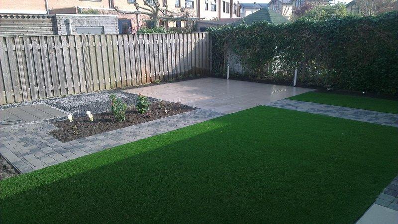 Moderne tuin met beplanting kunstgras en keramiek tegels den
